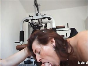 Pierced granny gets an anal invasion workout in the gym